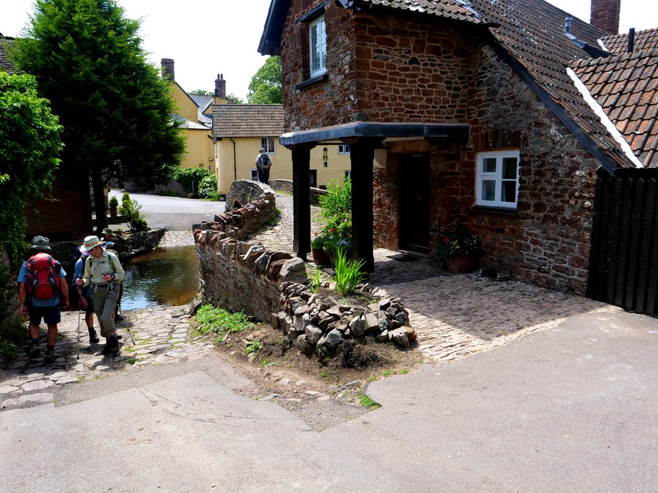 Allerford, a ford, packhorse bridge and a house built out over the path.