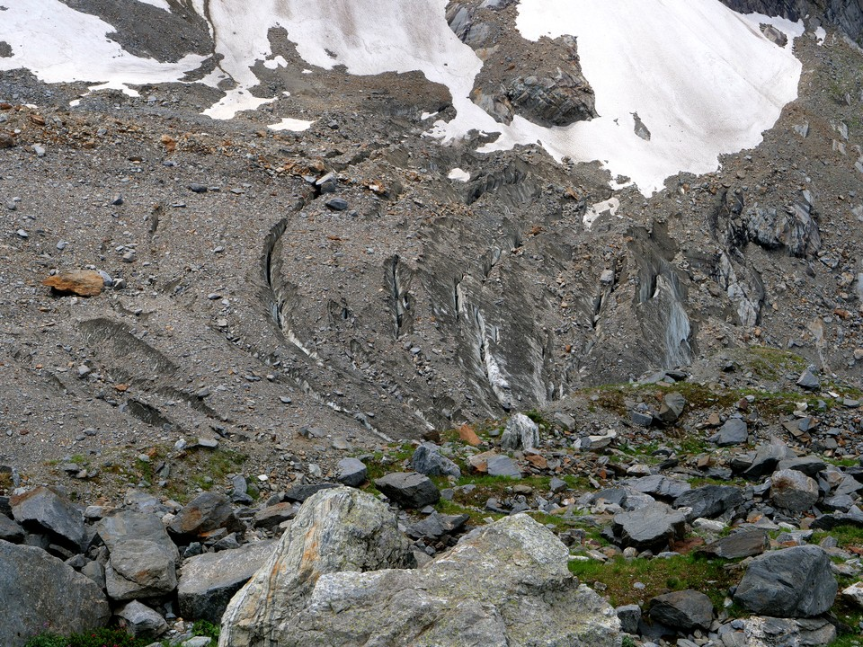 In places the glacier is covered with stone, but the crevases show the ice below