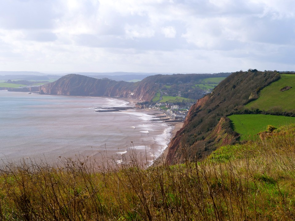 The view from Higher Dunscombe Cliff, just before Salcombe Mouth looking west over Sidmouth The tall cliff beyond is High Peak