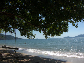 2012-12-03-04-35-41_p1090035_south-west-beaches-on-ko-chang.jpg  Probably the scene of many photos every day. A swinging seat under a tropical tree, blue seas and distant mountains.