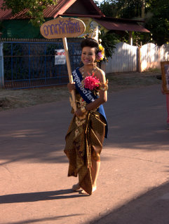 2012-12-28-02-59-47_p1090653_kumphawapi-school-procession.jpg  She is wearing a traditional brown skirt with gold decoration. her hair is also decorated with flowers. A procession of costumes traditional and modern through Kumphawapi by the members of the School