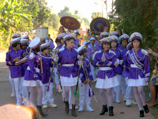 2012-12-28-03-08-05_p1090670_kumphawapi-school-procession.jpg  This school band is dressed in purple and white - and makeup! A procession of costumes traditional and modern through Kumphawapi by the members of the School